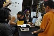 Student playwrights signing books during the reception.